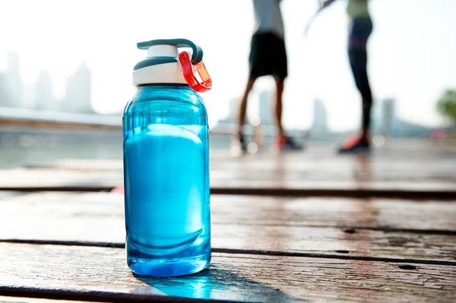 Dvaja muži v pozadí po športovej aktivite, pred ktorými je položená modrá fľaša s vodou