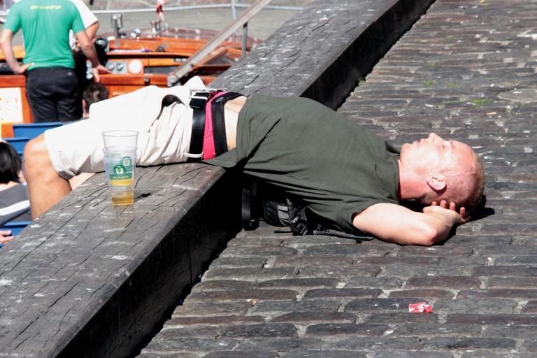 Spiaci človek na verejnosti, opilec, poháre od piva