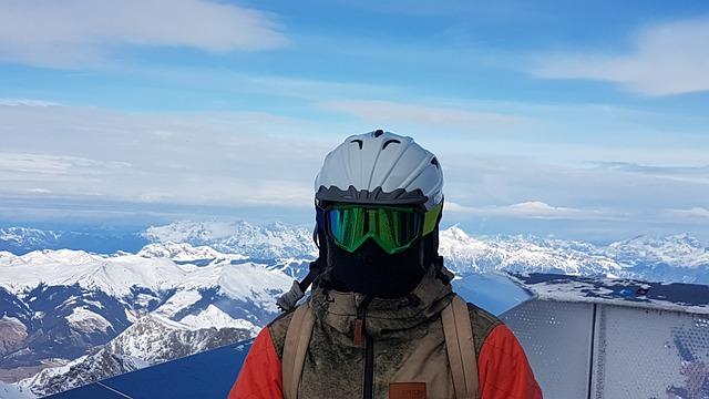 Človek v lyžiarskom oblečení, v okuliaroch a v prilbe