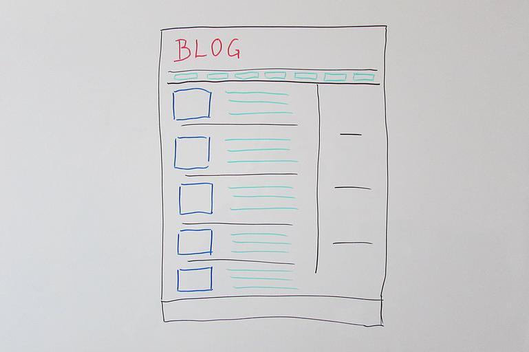 Nákres papiera s kolónkami a nápisom BLOG na bielej tabuli