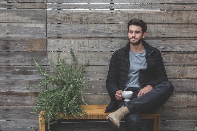 Muž sedí pri drevenej stene a pije kávu
